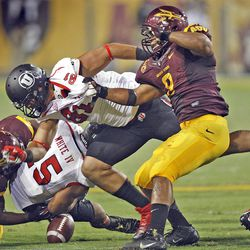Utah Utes running back John White (15) fumbles the ball as he is hit by Arizona State Sun Devils safety Chris Young (21) and Utah Utes tight end Kendrick Moeai (81) tries to block out Arizona State Sun Devils linebacker Brandon Magee (8)as the Univeristy of Utah and Arizona State University play PAC 12 football Saturday, Sept. 22, 2012, in Tempe, Arizona.