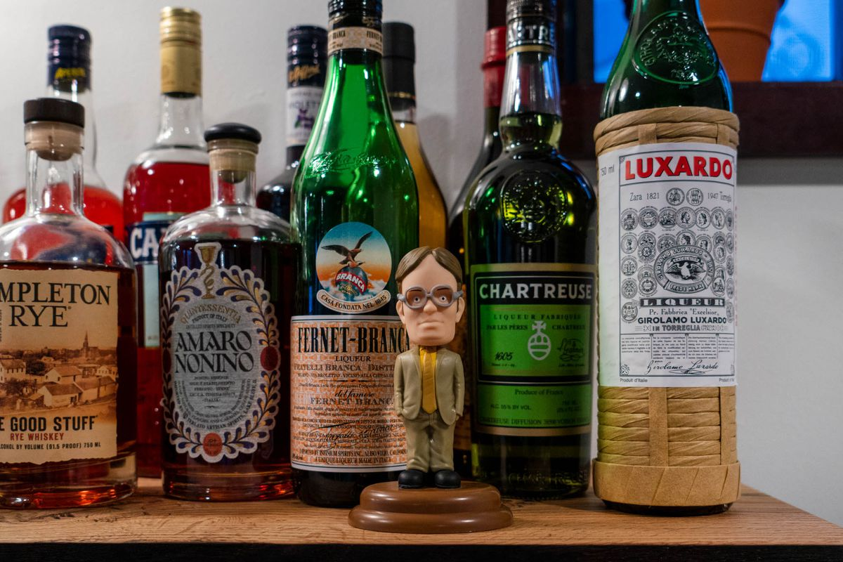 A collection of liquor bottles with a Dwight Schrute bobblehead doll displayed in front.