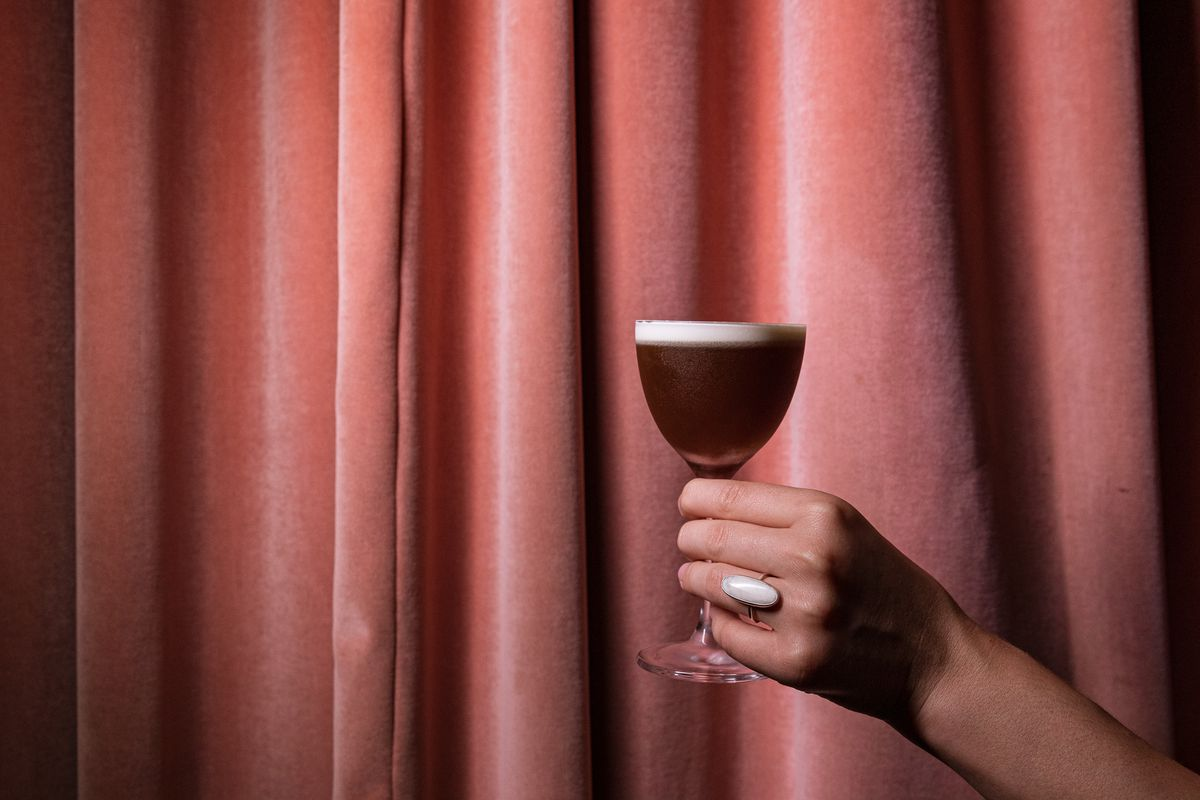 a coup glass filled with a dark brown cocktail with a white cream top that's held in a woman's hand with a ring on in front of a pink curtain