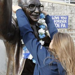 Beth Jenkins of Woodrings Floral Gardens puts a blue and white carnation lei around the neck of the statue of former Penn State football coach Joe Paterno as she helps deliver more than 1400 carnations outside Beaver Stadium before the NCAA football team's annual Blue White scrimmage on Saturday, April 21, 2012, in State College, Pa.