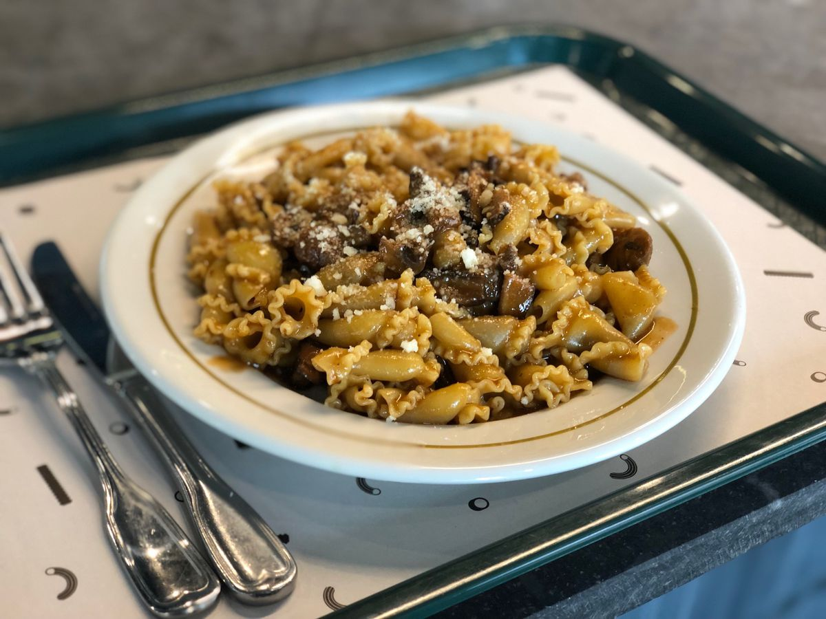 A bowl of mushroom campanelle pasta on a tray lined with a paper sheet, and a knife and fork to the left of the bowl.