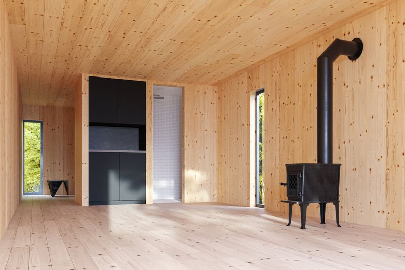 Interior of cabin lined in cedar wood with a black wood burning stove.