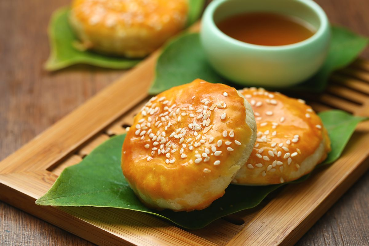 Wife cakes, or sweetheart cakes, sprinkled with sesame are presented on a palm leaf with tea.