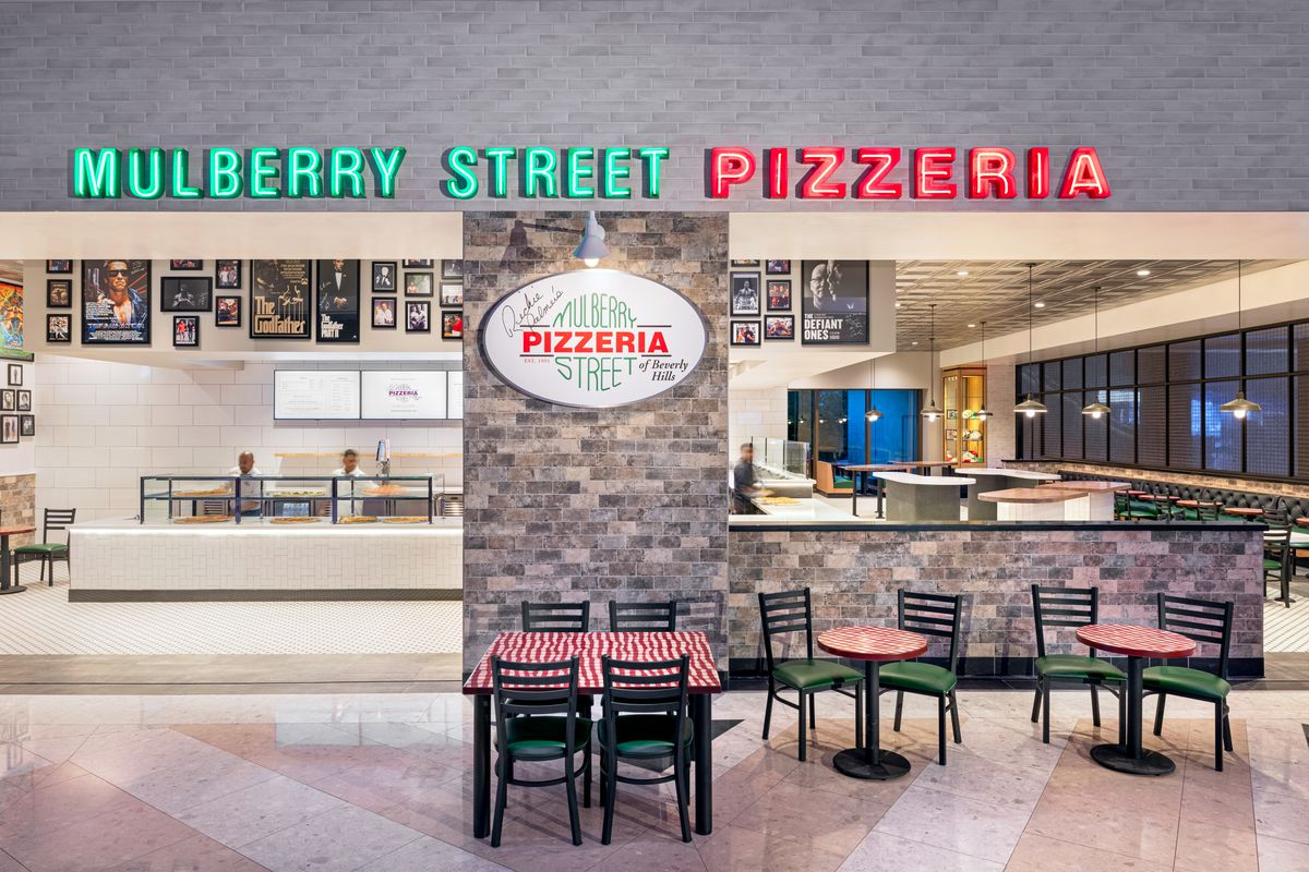 The exterior of a pizza shop with red and green lights saying Mulberry Street Pizzeria.