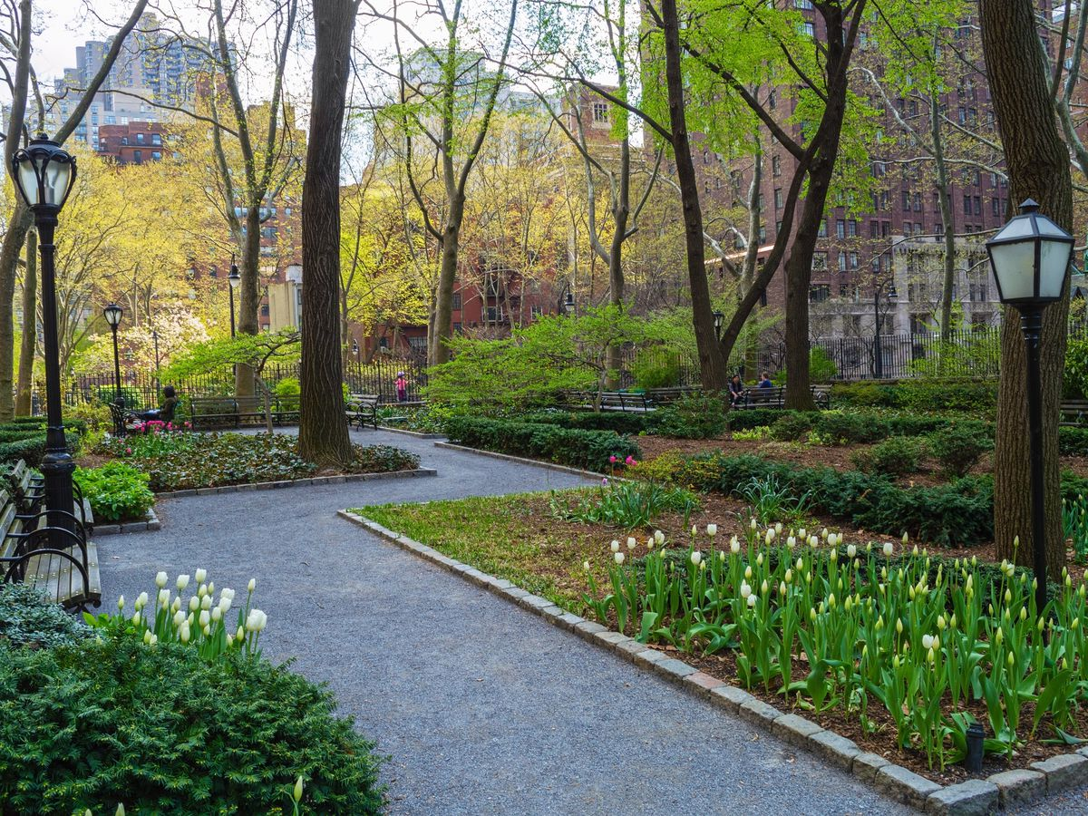 A path in Tudor City Greens in New York City. There are various plots with blooming flowers and trees.