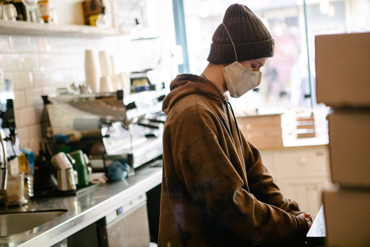 A service staff working behind the counter at Kahaila, a coffee shop