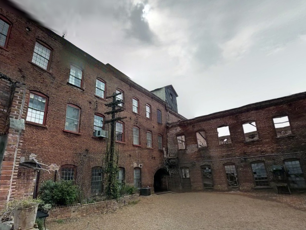 An abandoned building with a red brick facade and multiple windows without any glass windowpanes.