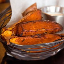 """Sweet Potato fries: these are fries (or in the above case, potato wedges) made from sweet potatoes instead of regular potatoes. They are orange! And sweetish!<br /><br />Found at: Blue Smoke, Great Jones Care, The Half King<br /><br />Photo via <a href=""""h"""