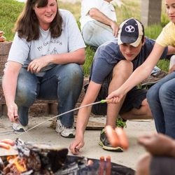 Pierce, 15, Hannah, 13, and Deanne Walker roast hot dogs in the family's backyard fire pit after a long, productive day of yard work. The family enjoys activities in their backyard, one of their favorites being the giant slip-n-slide that they set up every summer.