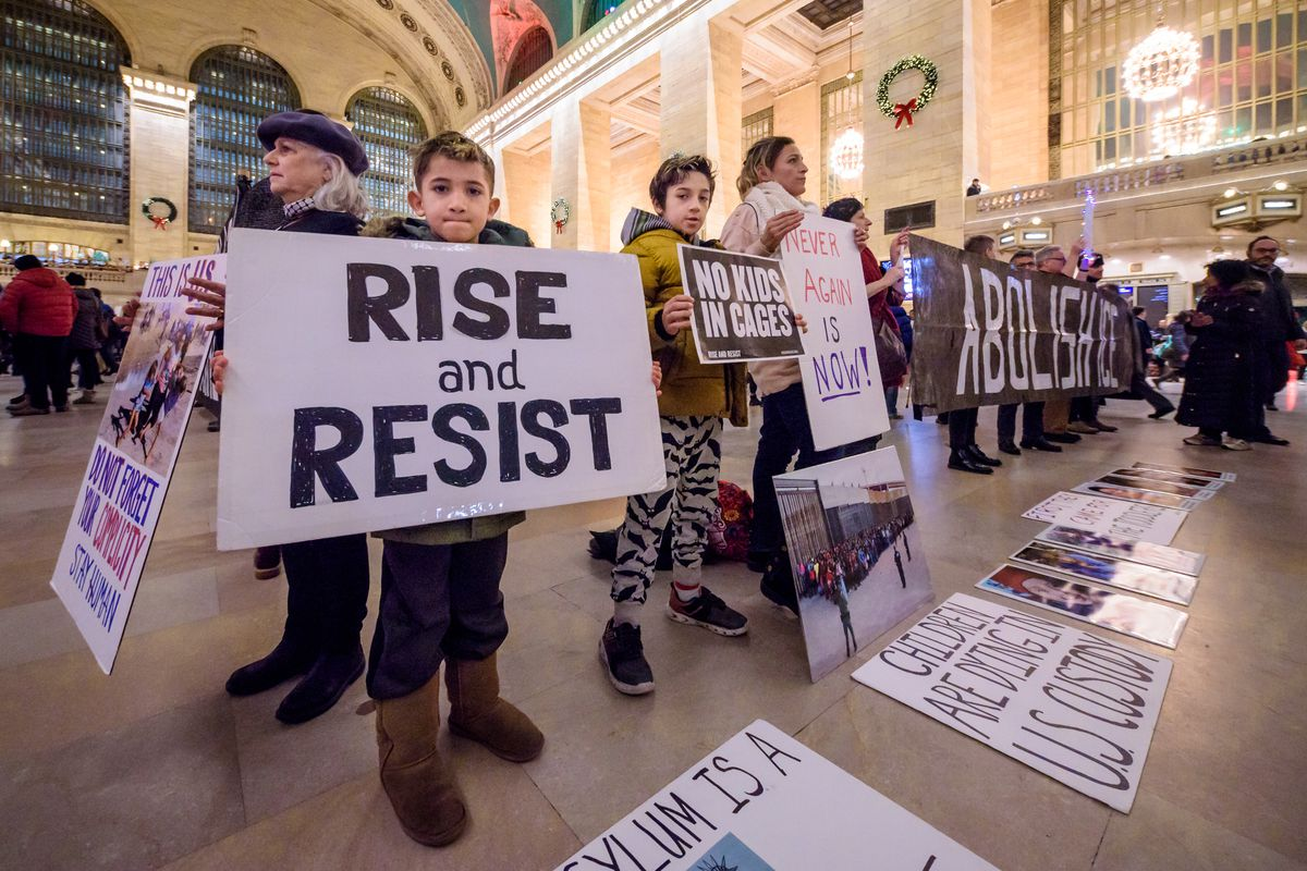 """Children hold signs beneath the arches of Grand Central Station reading """"Rise and Resist,"""" """"Children are dying in US custody,"""" and """"No Kids in Cages."""" Behind them, adults hold a black and white banner reading, """"Abolish ICE."""""""
