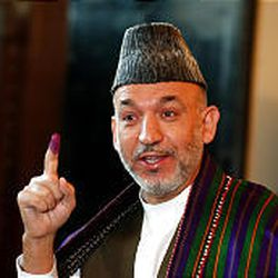 Afghan President Hamid Karzai shows his inked finger before voting in Kabul, Afghanistan, Sunday.