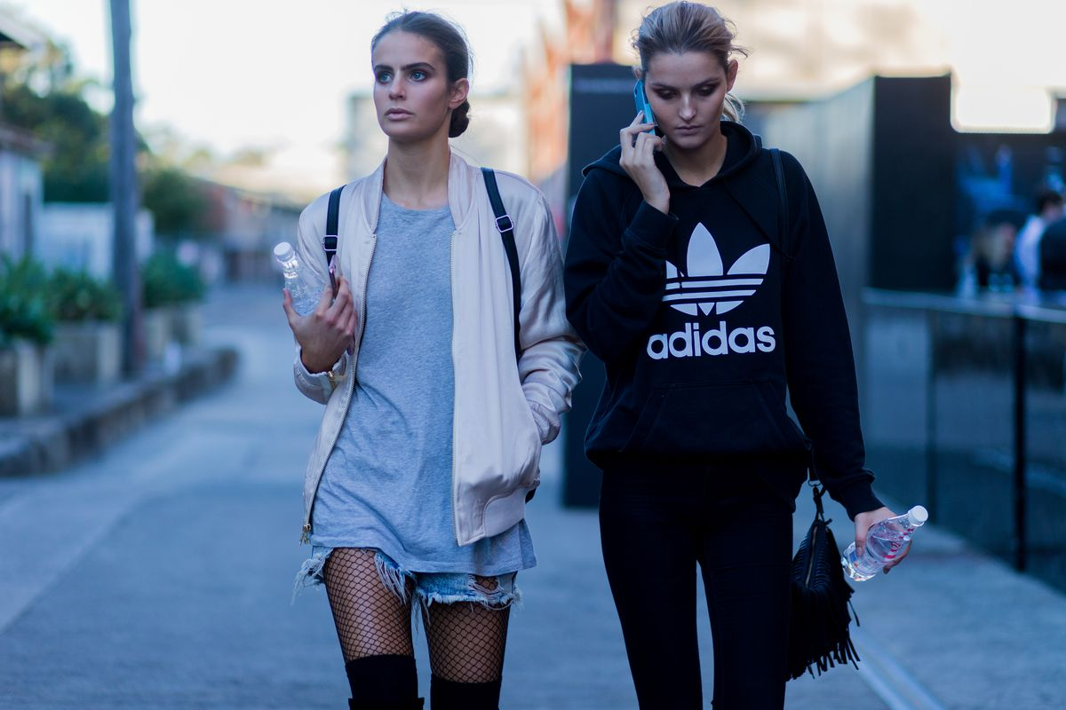 Two women walk down the street in distressed clothing.