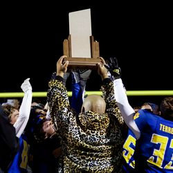 Orem head coach Gabe Sewell holds up the trophy as his team celebrates their win over Timpview in the 5A football state championship game at Cedar Valley High in Eagle Mountain on Friday, Nov. 20, 2020.