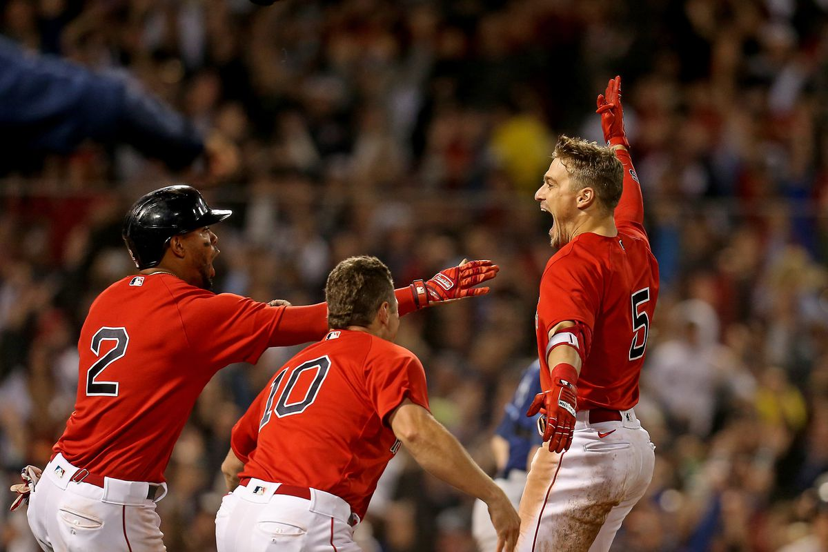Enrique Hernandez #5 of the Boston Red Sox celebrates with Xander Bogaerts #2 and Hunter Renfroe #10 after hitting a sacrifice fly, scoring Danny Santana to win Game 4 of the ALDS against the Tampa Bay Rays at Fenway Park on October 11, 2021 in Boston, Massachusetts.