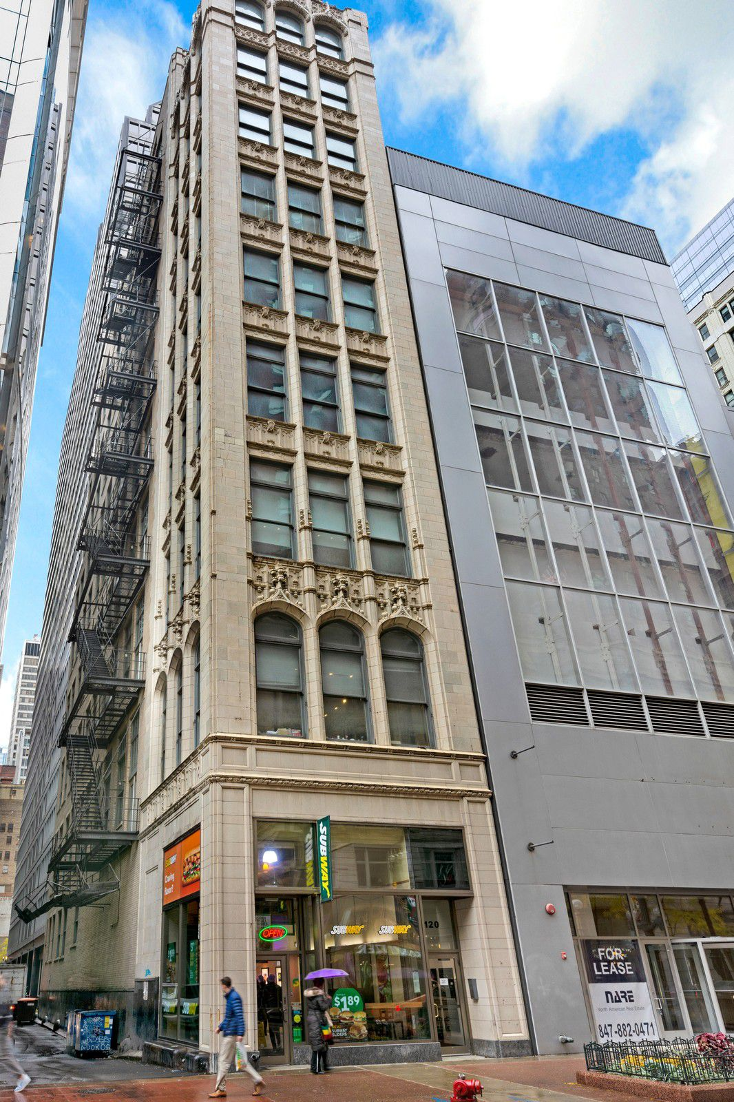 A historic office building in a dense urban setting. There is gothic details on the exterior and a metal fire escape over the alleway.