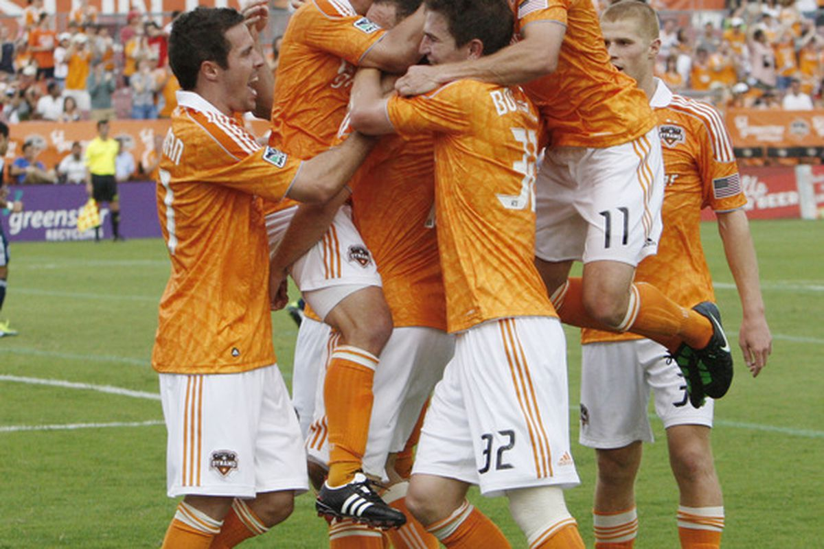HOUSTON - APRIL 10:  Bobby Boswell #32 of the Houston Dynamo is mobbed by his teammates after scoring in the first half at Robertson Stadium on April 10, 2011 in Houston, Texas.  (Photo by Bob Levey/Getty Images)