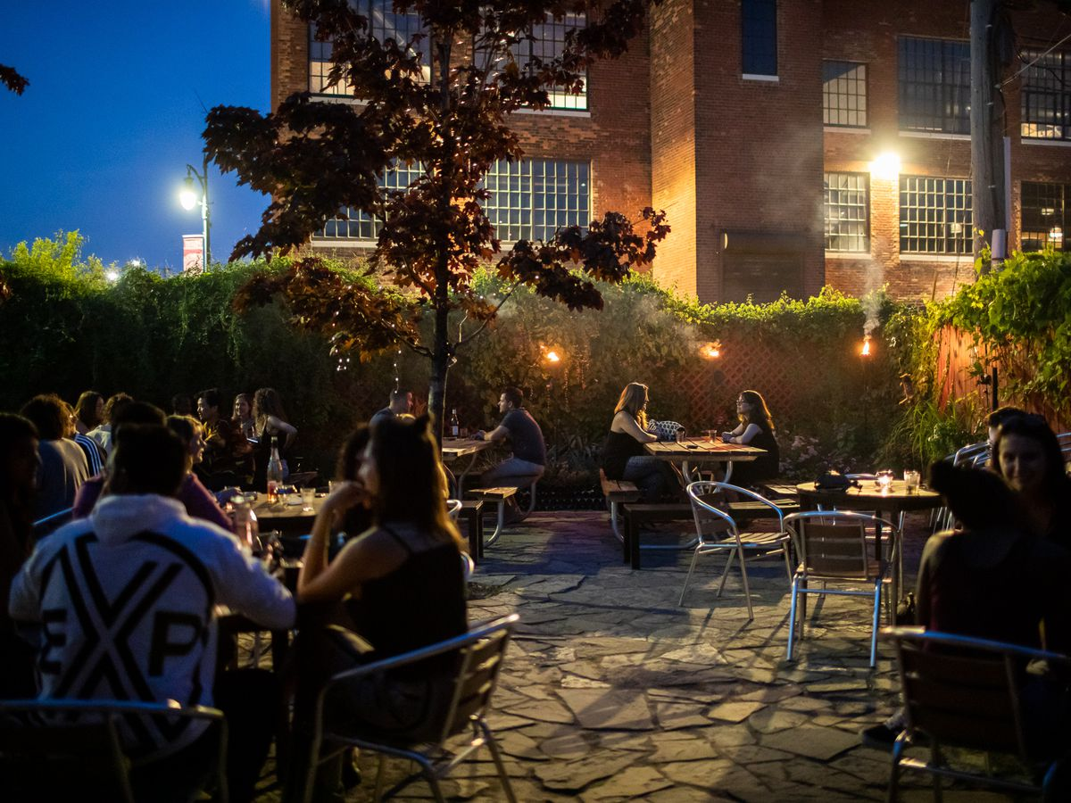 The patio at Motor City wine is full of people after dar. The fence with ivy is lit up with tiki torches.