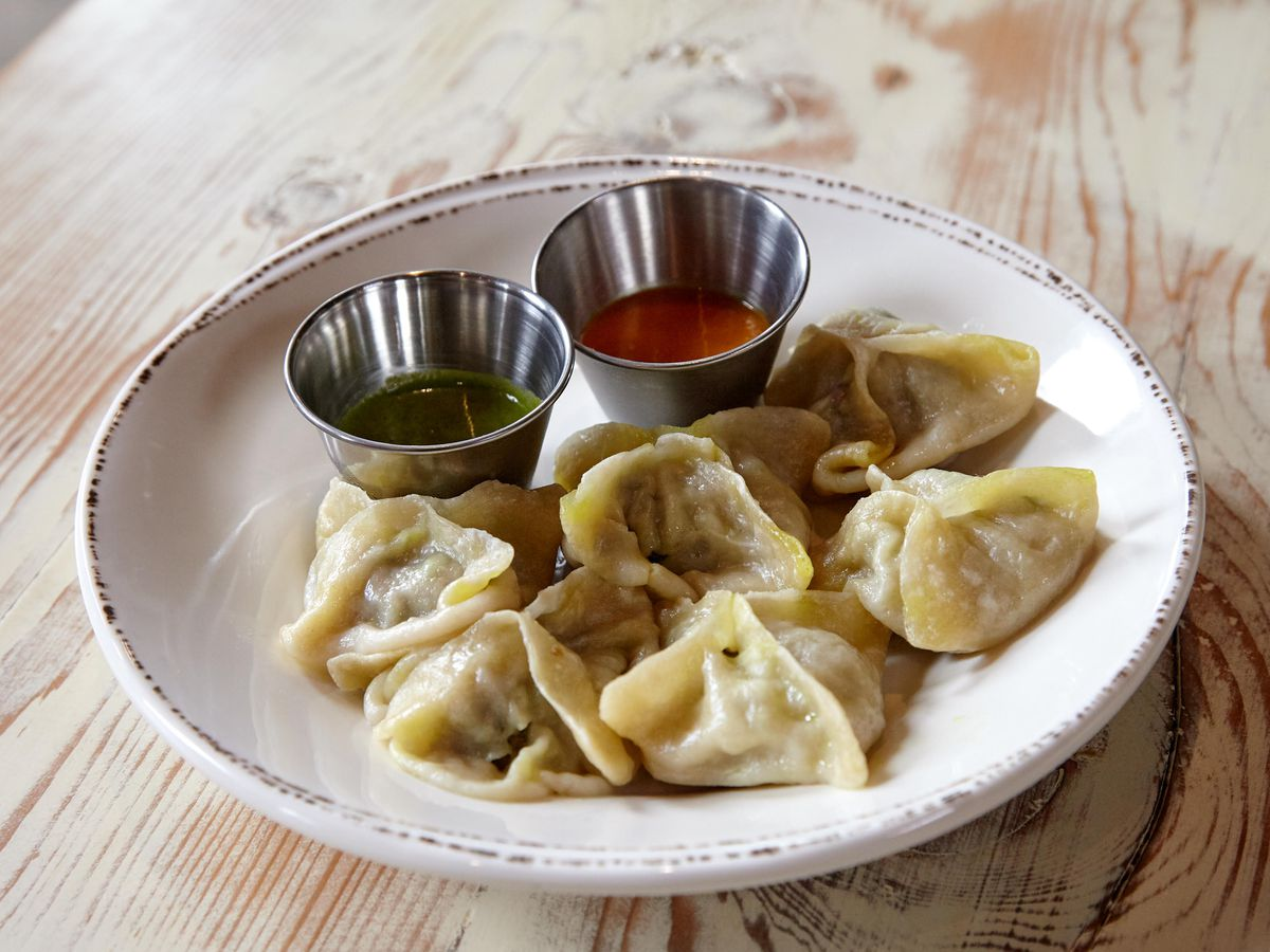 Dumplings on a white ceramic plate with a duo of sauces