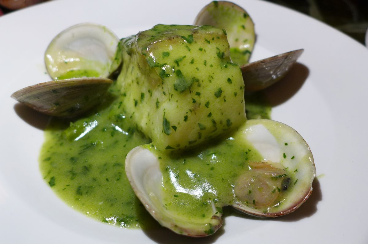 A chunk of cod and handful of clams smothered in green sauce.