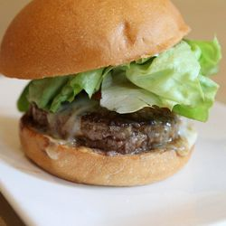 Cali burger, with lettuce, roasted tomato, caramelized onions, house spread, and American cheese