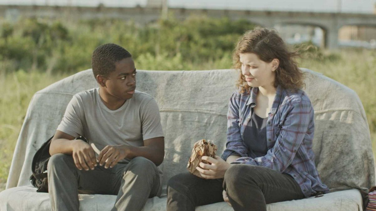 a young black boy and a middle-aged white woman sit on a couch on the side of the road