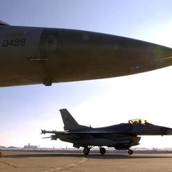 Lt. Col. David Lucia, rear, taxis his fully armed F-16 fighter jet past a parked aircraft on his way to the runway for takeoff Thursday, Feb. 14, 2002, at Hill Air Force Base, in Ogden. The first F-16 touched down at Hill Air Force Base 30 years ago, signifying the beginning of what has been an historic relationship between the base and fighter jet.