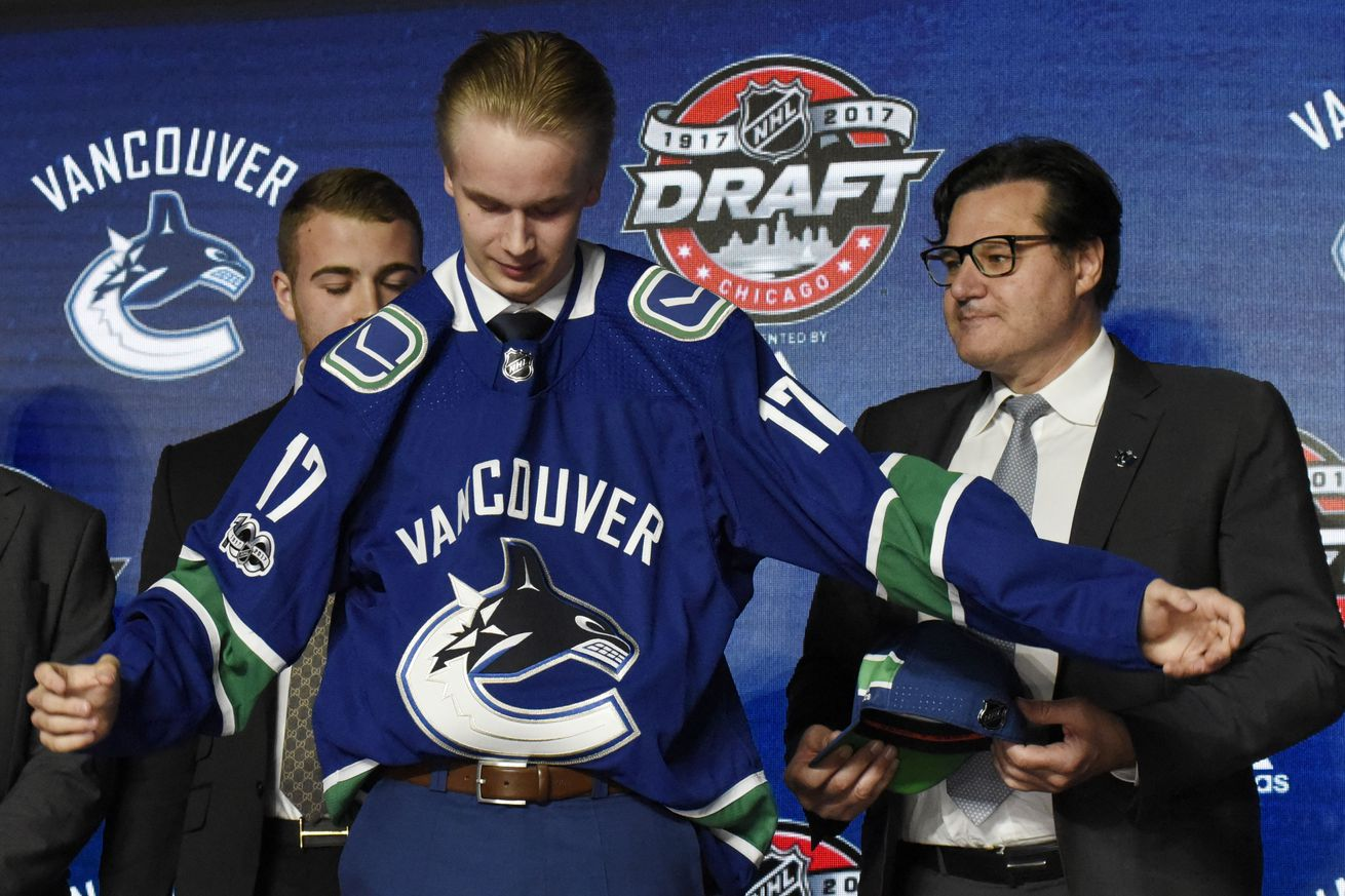 June 23, 2017; Chicago, IL, USA; Elias Pettersson puts on a team jersey after being selected as the number five overall pick to the Vancouver Canucks in the first round of the 2017 NHL Draft at the United Center. Mandatory Credit: David Banks