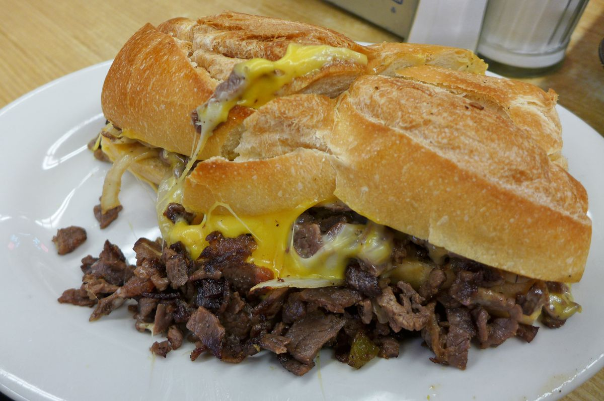 A Philly cheesesteak in a squished hero roll with nuggets of beef tumbling out, some smothered in melted American cheese...