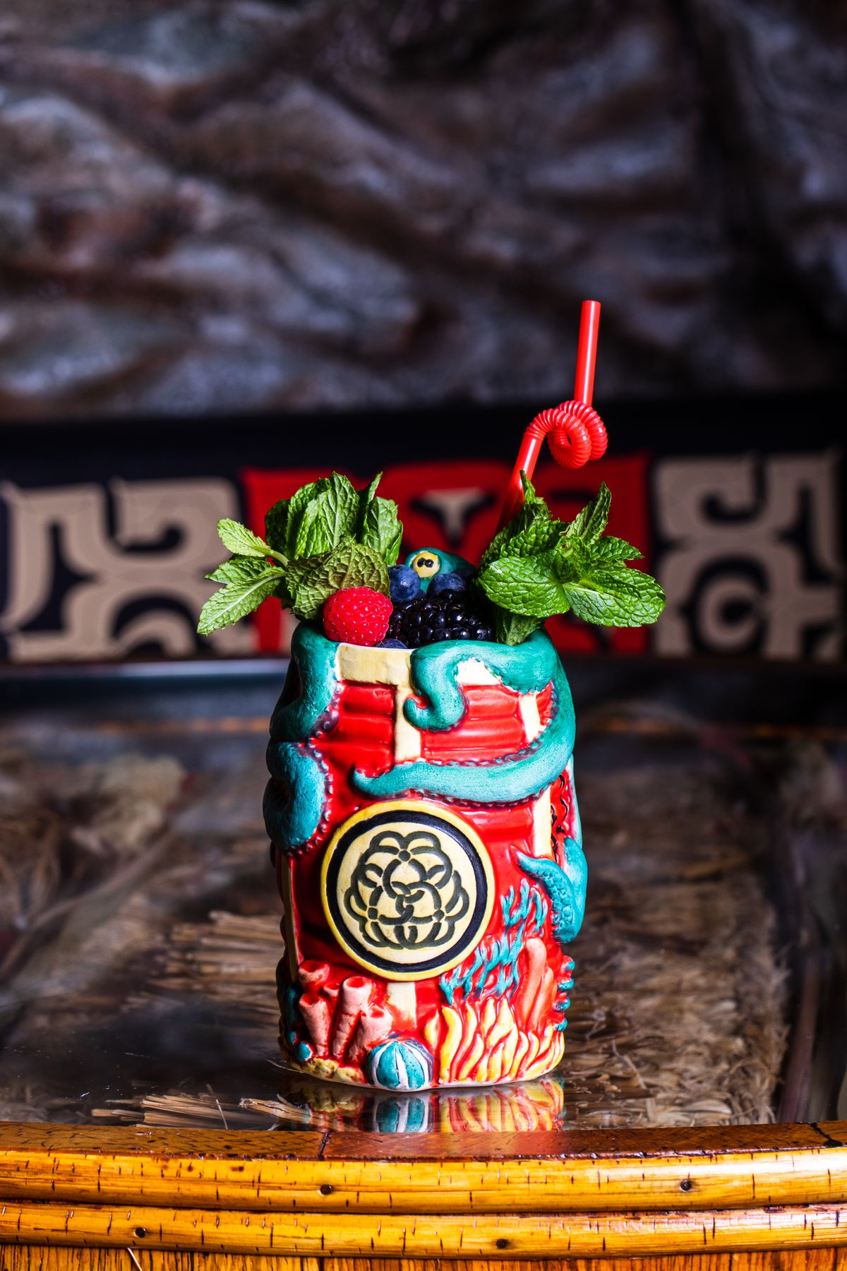 A mug in the shape of a red barrel is hugged by tentacles and garnished with green mint, berries, and a red twisty straw.