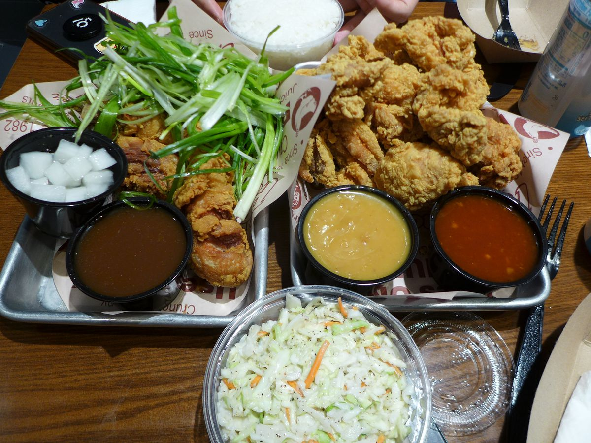Two trays of fried chicken with all sorts of toppings and dipping sauces on the side.