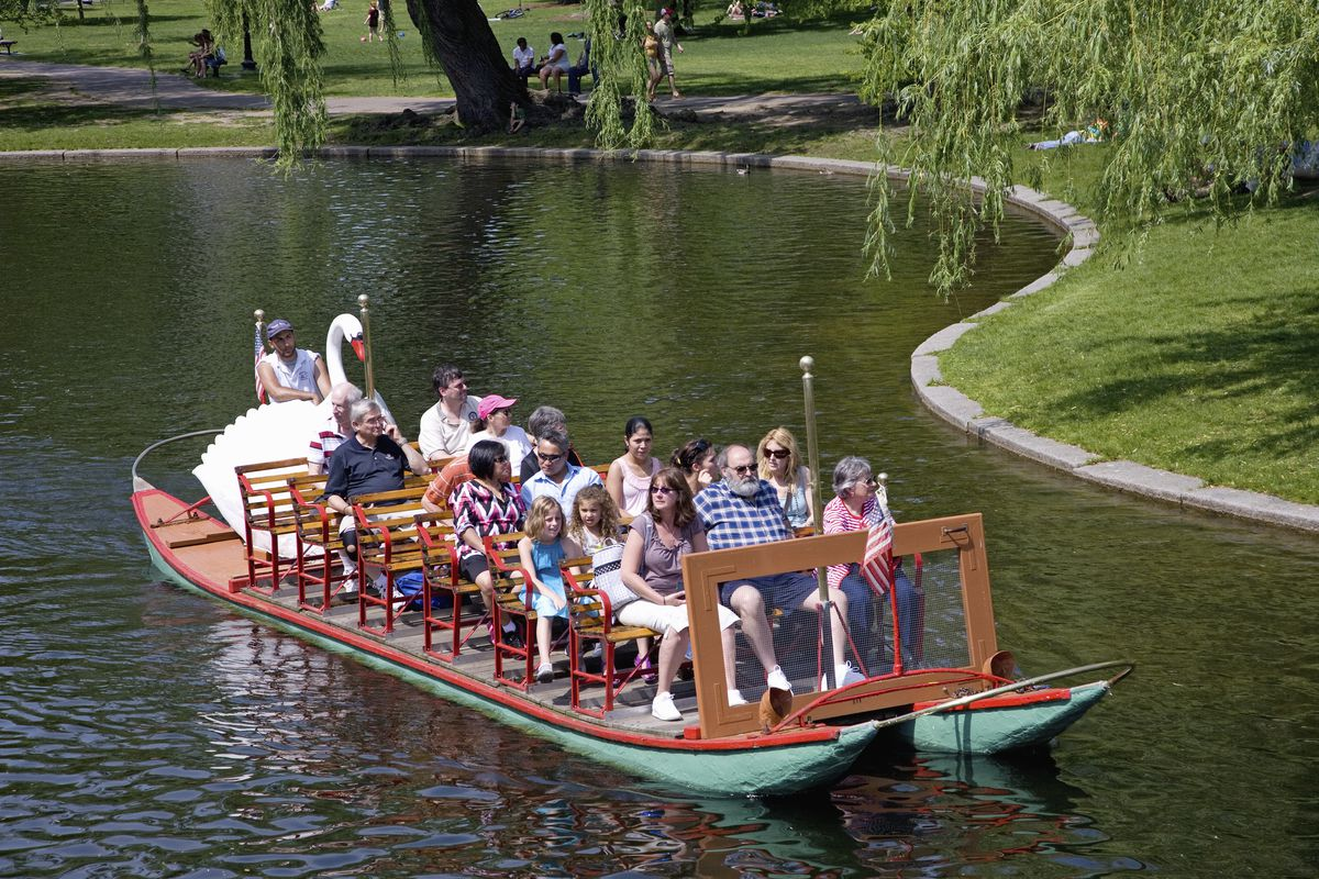 People sitting on chairs on a boat that is traveling through Boston Public Garden.