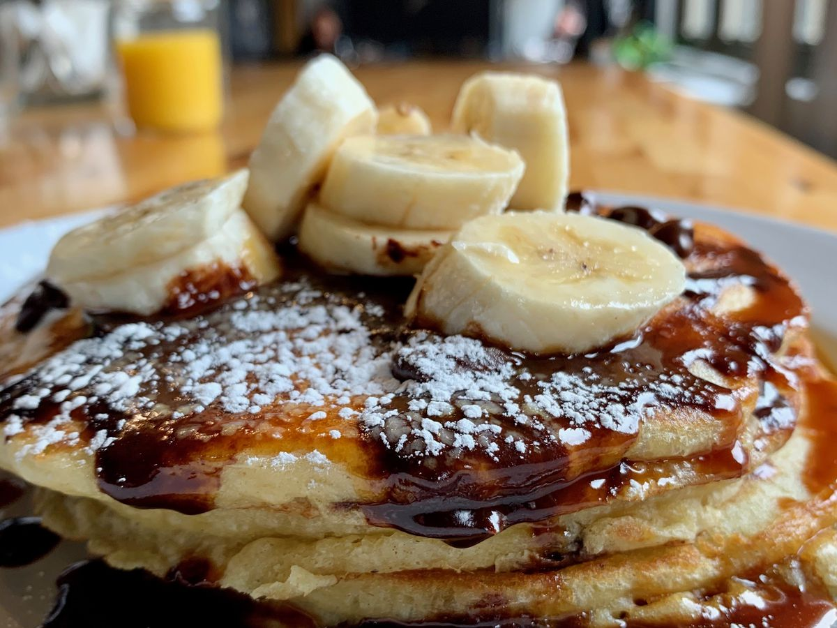 stack of pancakes with chocolate sauce, banana slices, and powdered sugar