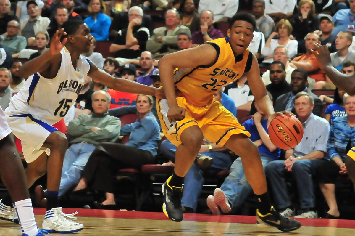 Jabari Parker of Simeon looks to move inside as Bloom's Johnny Griffin rushes to defend.