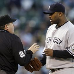 New York Yankees' CC Sabathia, right, is warned by home plate umpire Jerry Layne after throwing a pitch behind Oakland Athletics' Kurt Suzuki.