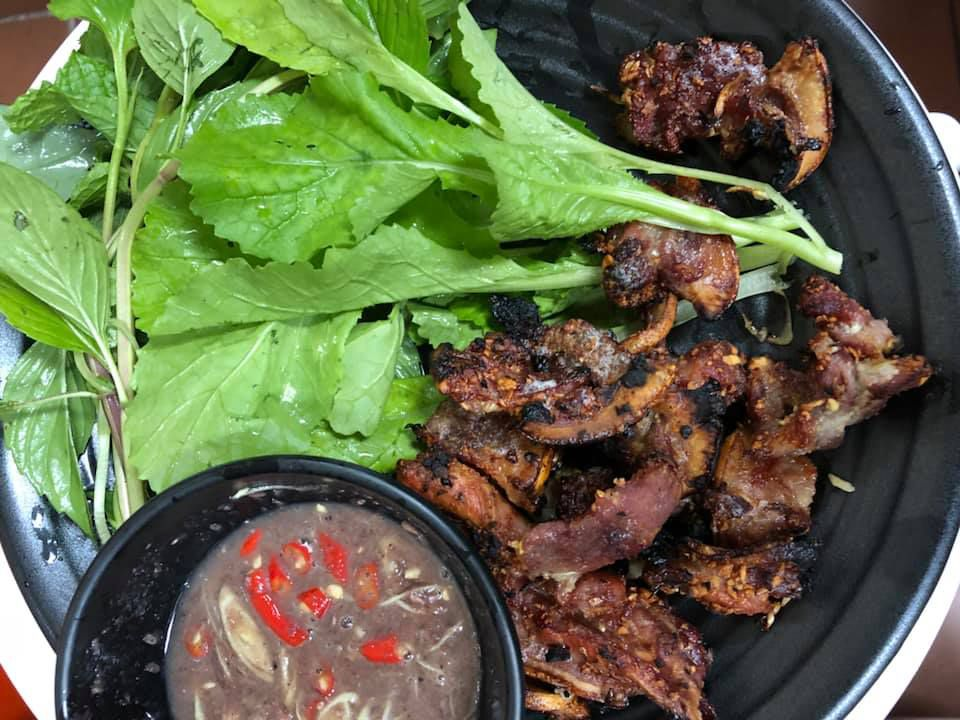 A dish of grilled boar with a spicy dipping sauce and greens