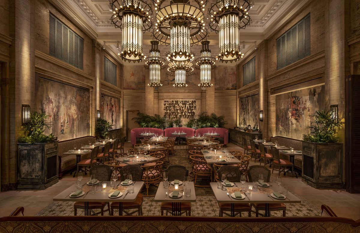 A high-ceilinged restaurant with grand chandeliers, red plush seating, and wood accents