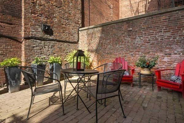 A brick patio next to a brick wall, and there is furniture on the patio.
