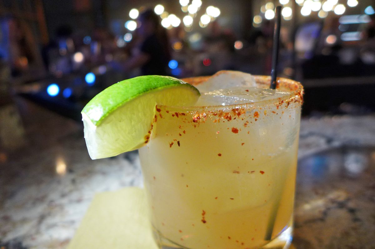 A cocktail glass with a mixed drink inside has a lime wedge stuck on the rim and a sprinkle of crushed red pepper.