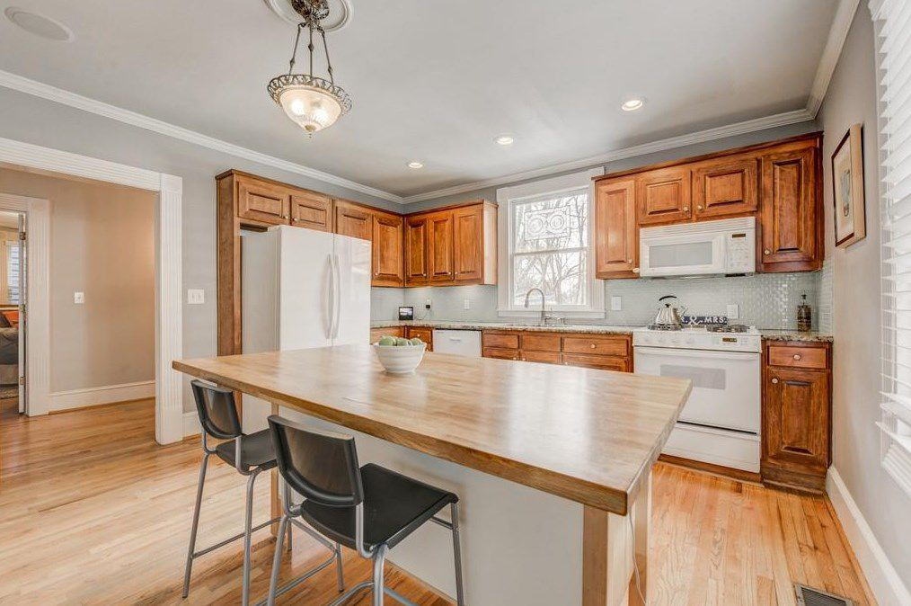 A kitchen with wood floors and cabinets.