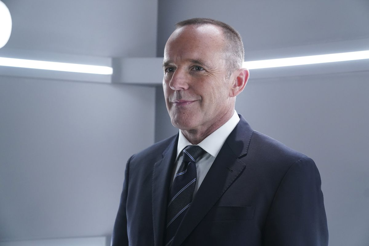 A man with short buzzed hair smirks — his face is smug. He stands against a neutral grey background with strip lights behind and is wearing a suit and tie.