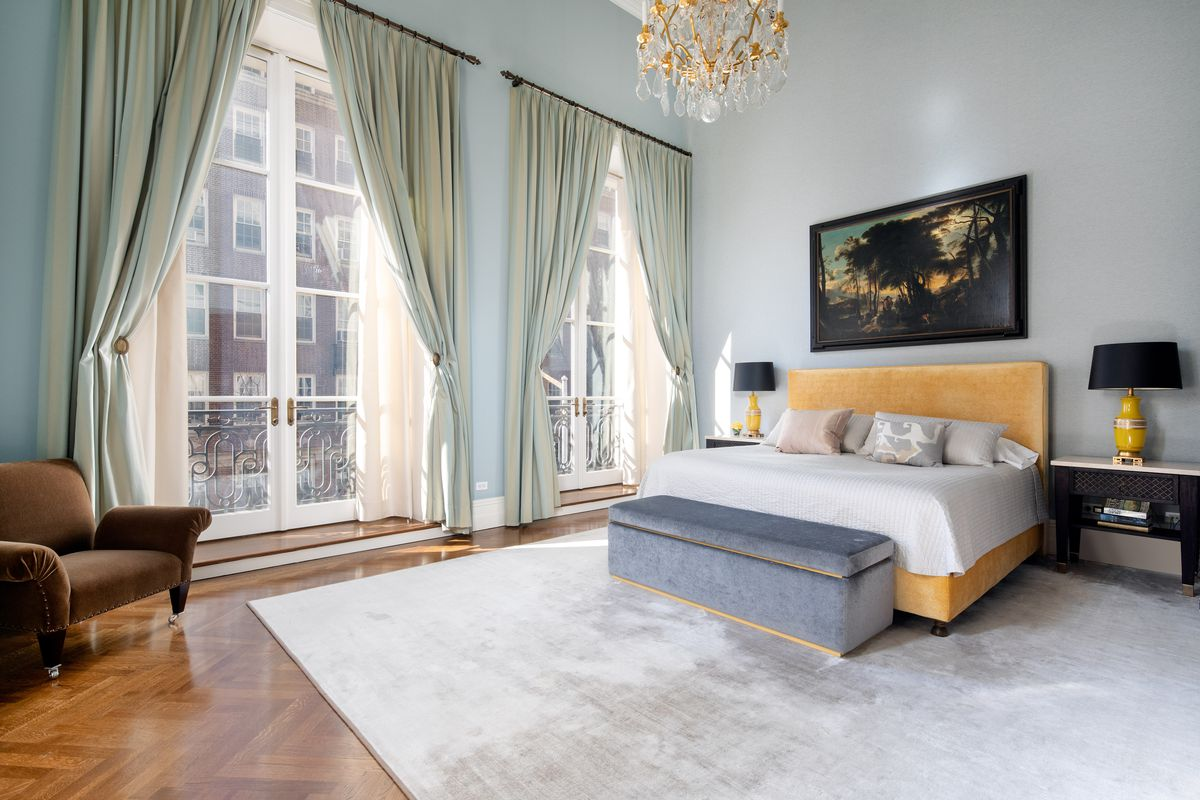 The master bedroom has French door windows, soaring ceilings, and a gold and crystal chendelier.