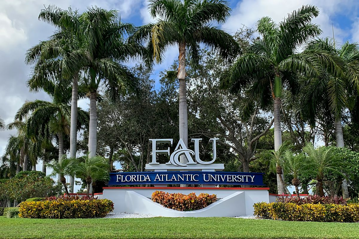 The entrance to Florida Atlantic University in Boca Raton Florida, featuring a sign and a grouping of palm trees.