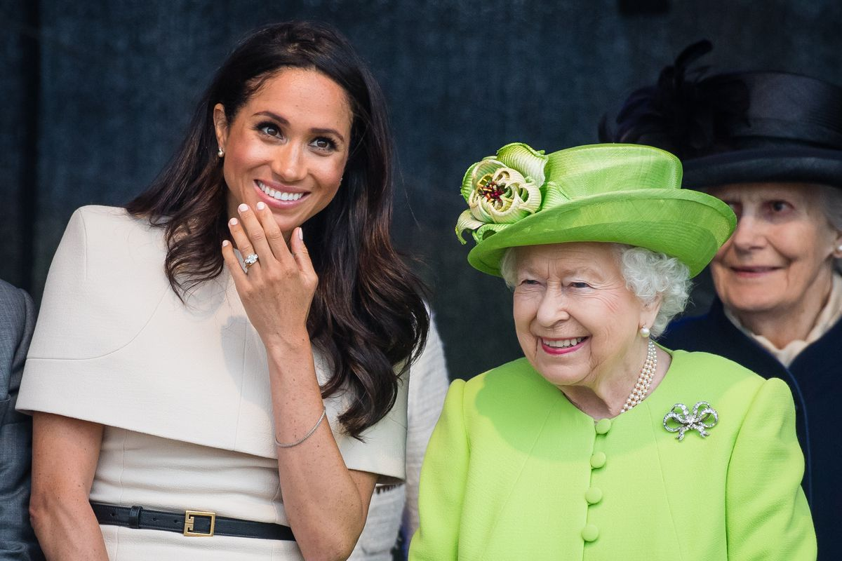 Markle and the Queen sit next to each other, laughing.