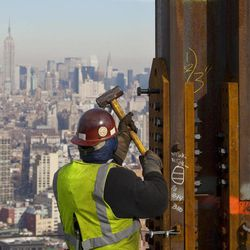 """FILE- In this Dec. 16, 2010, file photo, an ironworker connects a steel plate to a column at One World Trade Center in New York. The Empire State Building is visible in the rear upper left. One World Trade Center, the giant monolith being built to replace the twin towers destroyed in the Sept. 11 attacks, will lay claim to the title of New York City""""™s tallest skyscraper on Monday, April 30, 2012, as workers erect steel columns that will make its unfinished skeleton a little over 1,250 feet, just high enough to peak over the observation deck on the Empire State Building. The milestone is a preliminary one. The so-called """"Freedom Tower"""" isn""""™t expected to reach its full height for at least another year, at which point it is likely to be declared the tallest building in the U.S."""