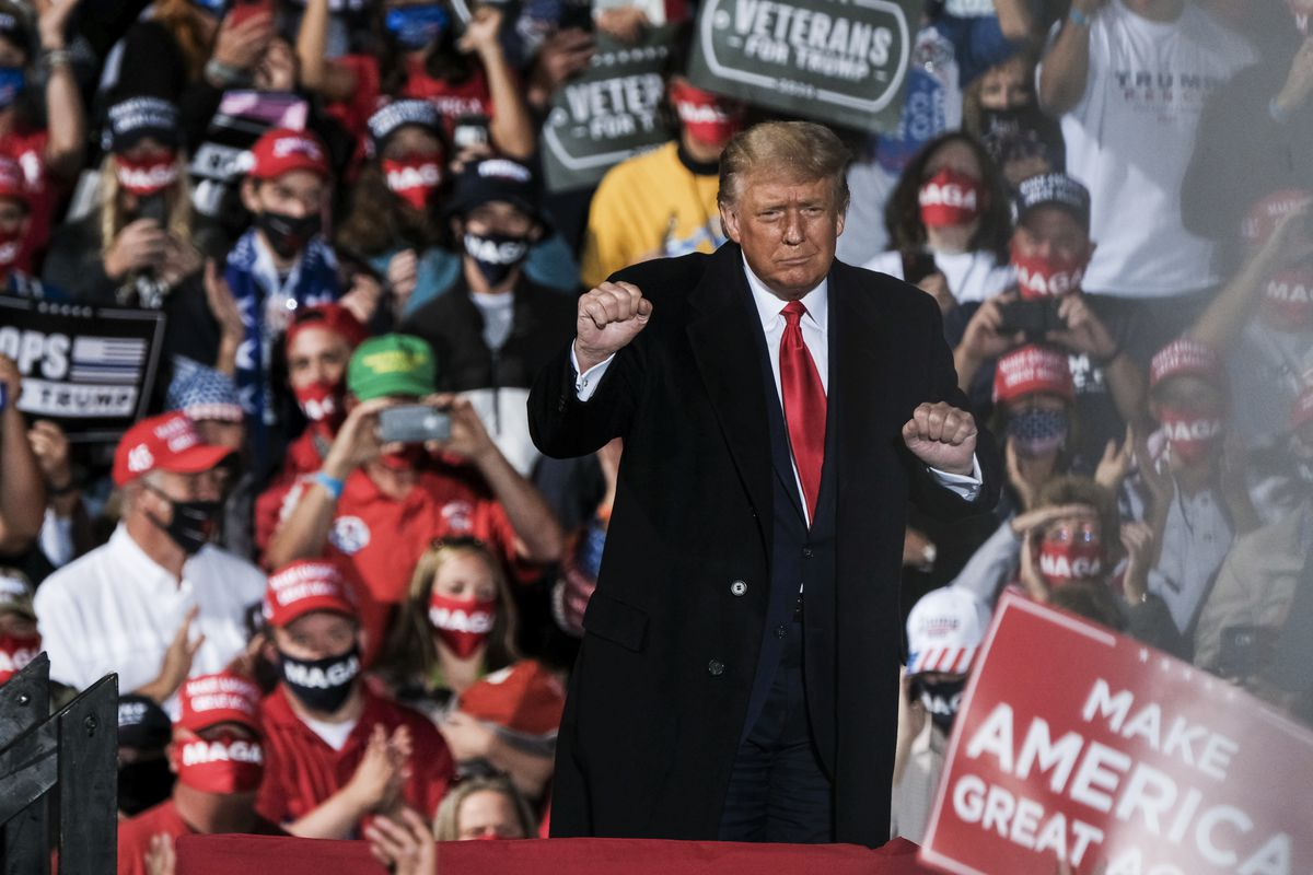 Trump onstage at a rally holding his fist up before a crowd.