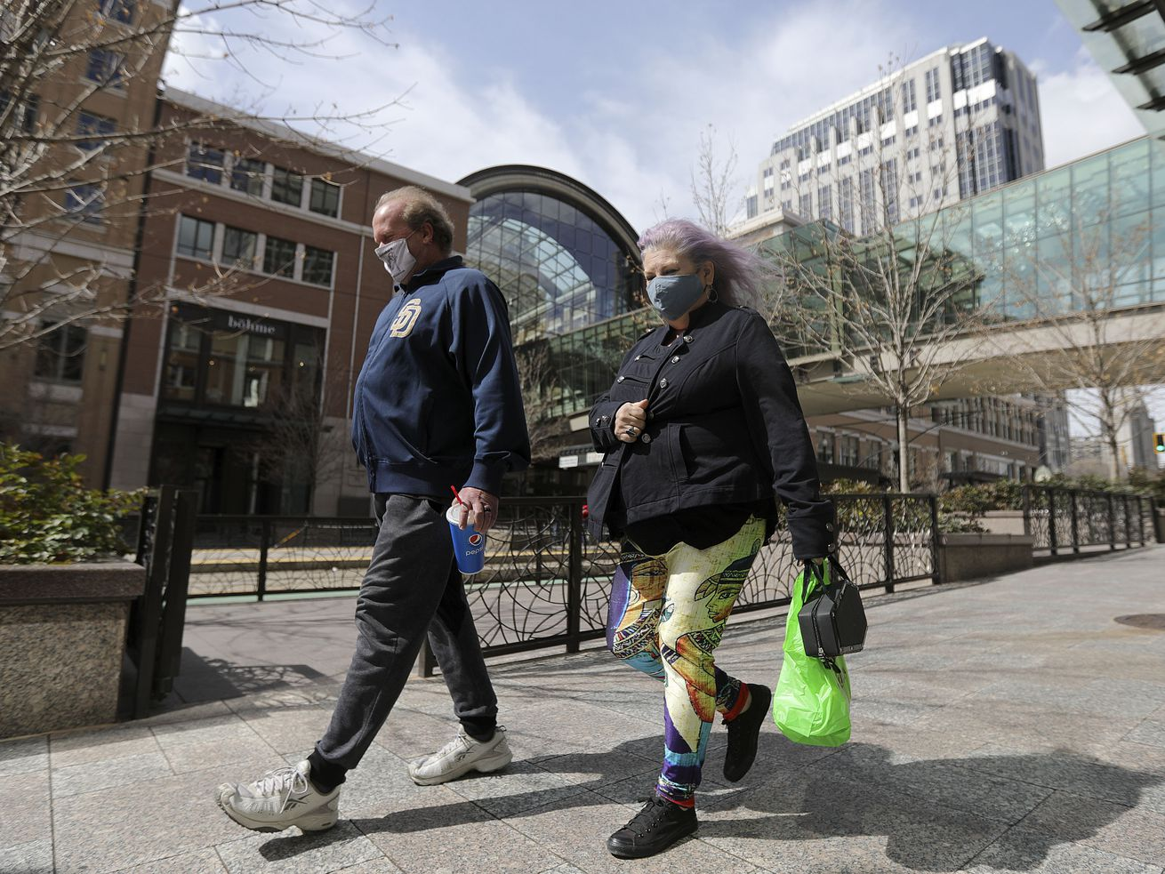 John Forker, left, and Jill Forker wear masks while walking in downtown Salt Lake City on Wednesday, March 24, 2021.