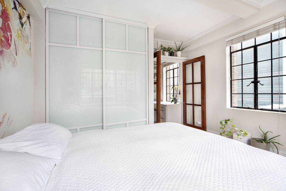 A corner bedroom with white walls and white bedding on a Queen sized bed.