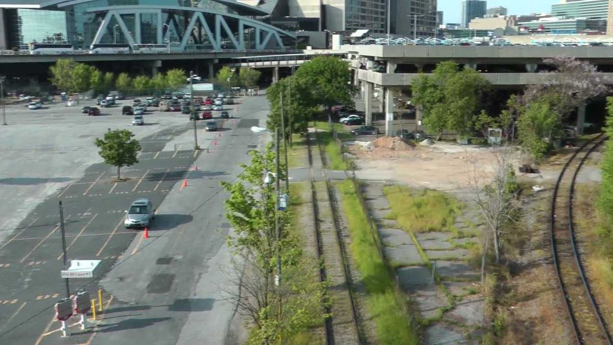 A view of the gulch, a large parking lot, and rail lines.