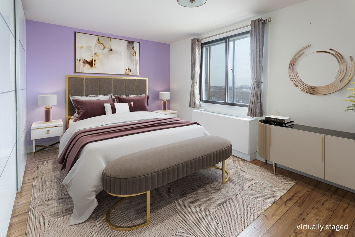 A bedroom with a purple wall, hardwood floors, a large bed, and a large window.