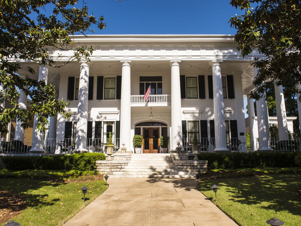 The exterior of a white house with columns and multiple windows. There is a path leading up to the house which has grass on both sides.